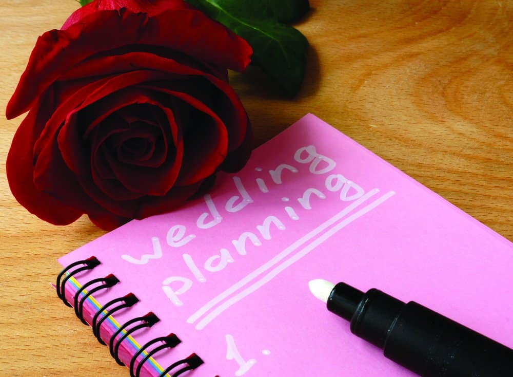 Pink notepad with wedding planning and rose