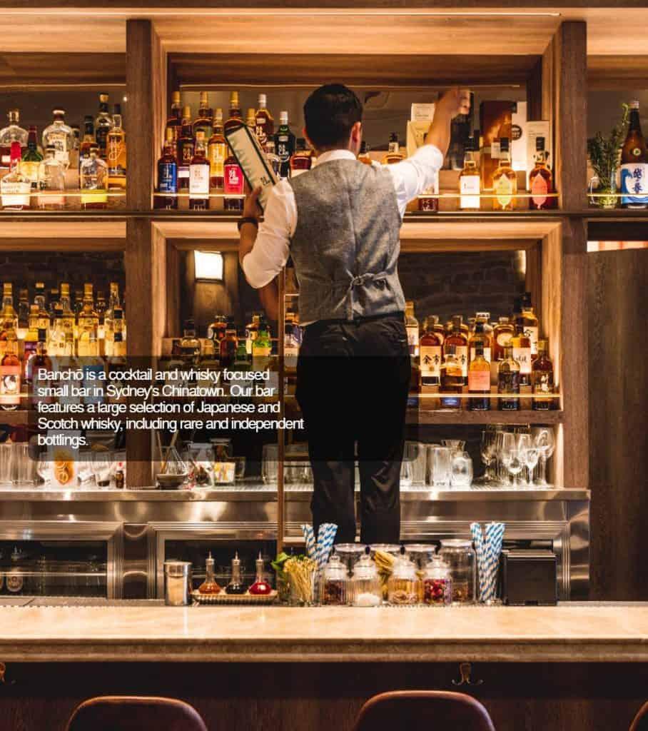 guy behind bar stocking shelves