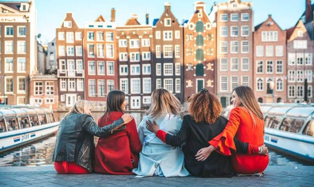 girls in amsterdam sitting in front of buildings