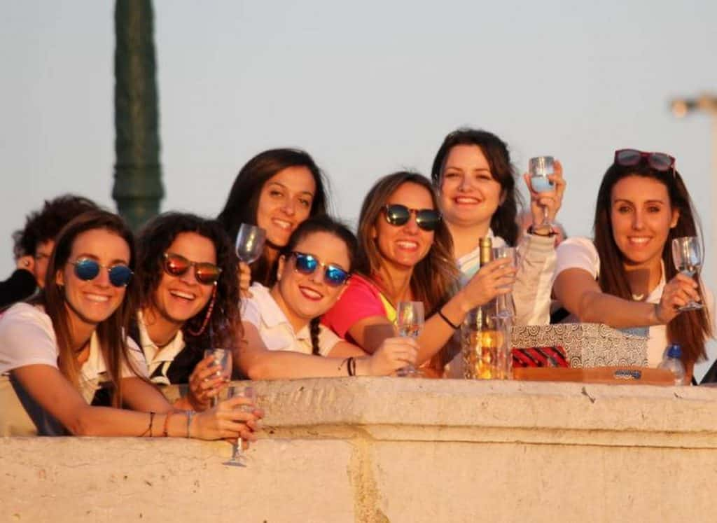 girls drinking along wall in madrid