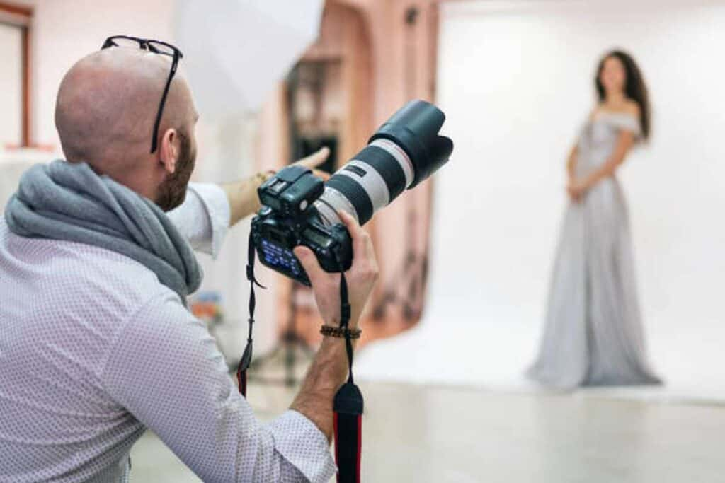 fashion photographer shooting a photo session with a model in a studio